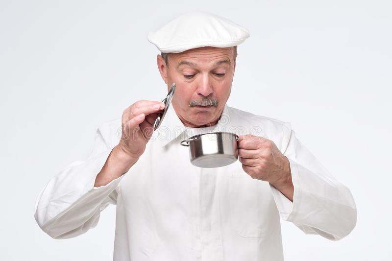 Senior chef cook holding small pan and looking inside it with surprise. royalty free stock image