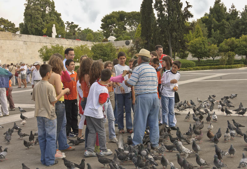 Senior and children with pigeons stock image