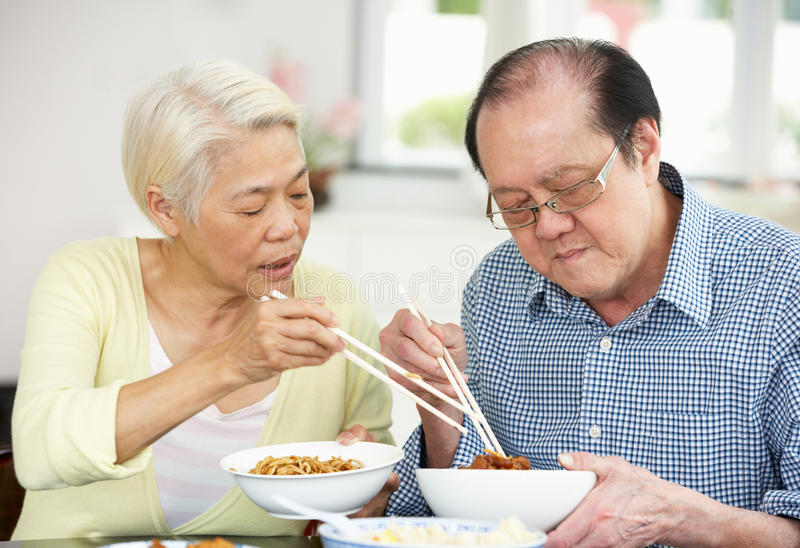 Download Senior Chinese Couple Sitting At Home Eating Meal Stock Image - Image: 26245525