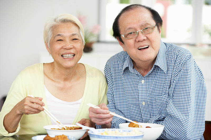 Download Senior Chinese Couple Sitting At Home Eating Meal Stock Photo - Image: 26245526