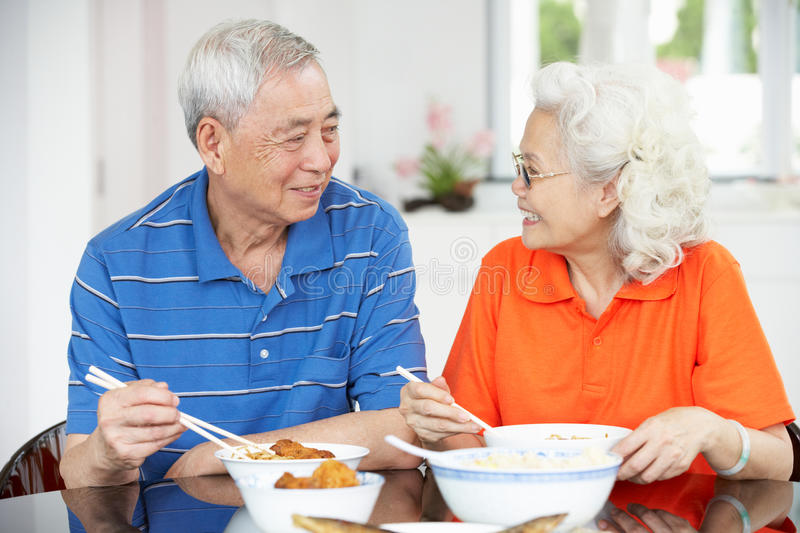 Senior Chinese Couple Sitting At Home Eating Meal royalty free stock images
