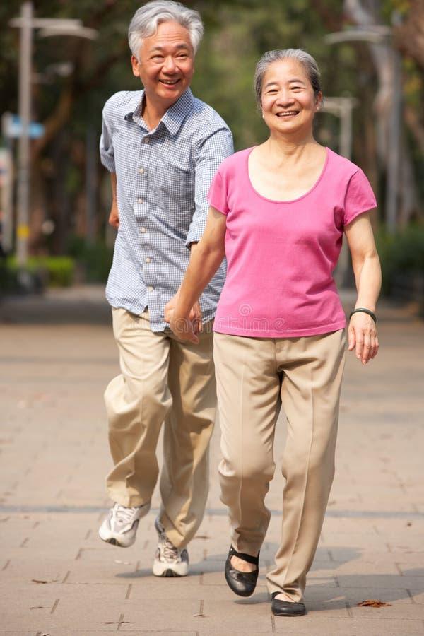 Download Senior Chinese Couple Walking In Park Stock Image - Image of walking, smiling: 26098363