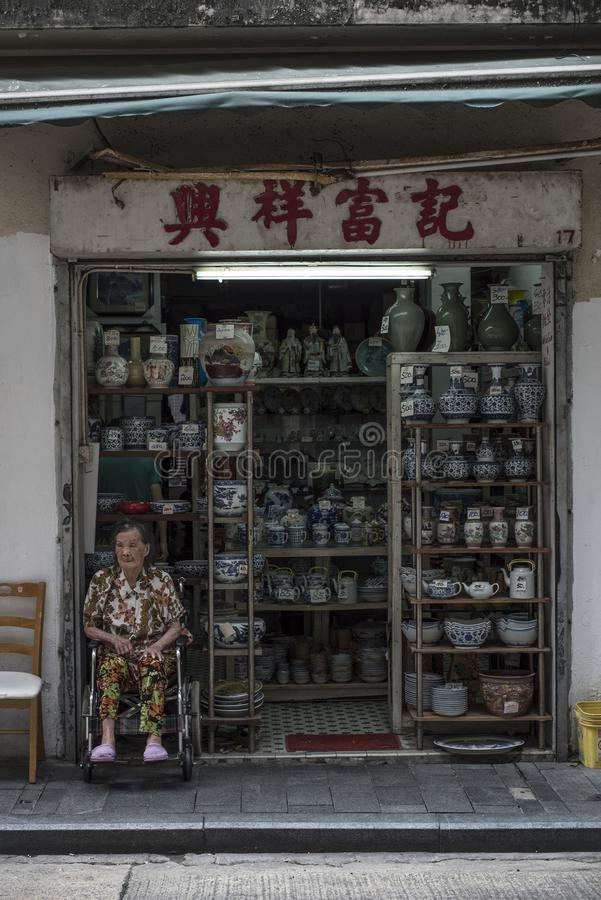 Senior Chinese woman sits by the family ceramics shop in Hong Kong. stock image