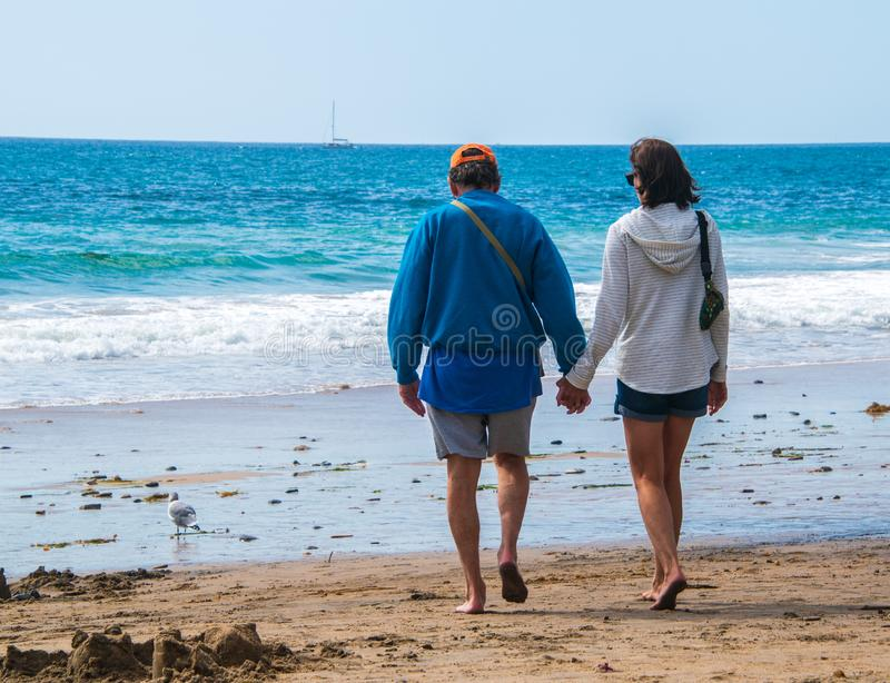 Senior citizen baby boomer male and female caucasian couple walking on the beach towards the ocean holding hands. stock images