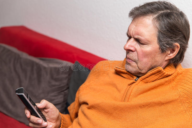 Senior citizen on a couch with phone. Is having problems royalty free stock image