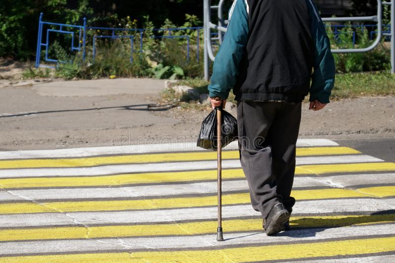 Senior citizen - an elderly man with a cane and a black bag crosses the road along a marked pedestrian crossing. Life in the city stock image