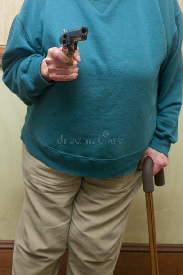 Senior Citizen Holding A Gun Royalty Free Stock Image