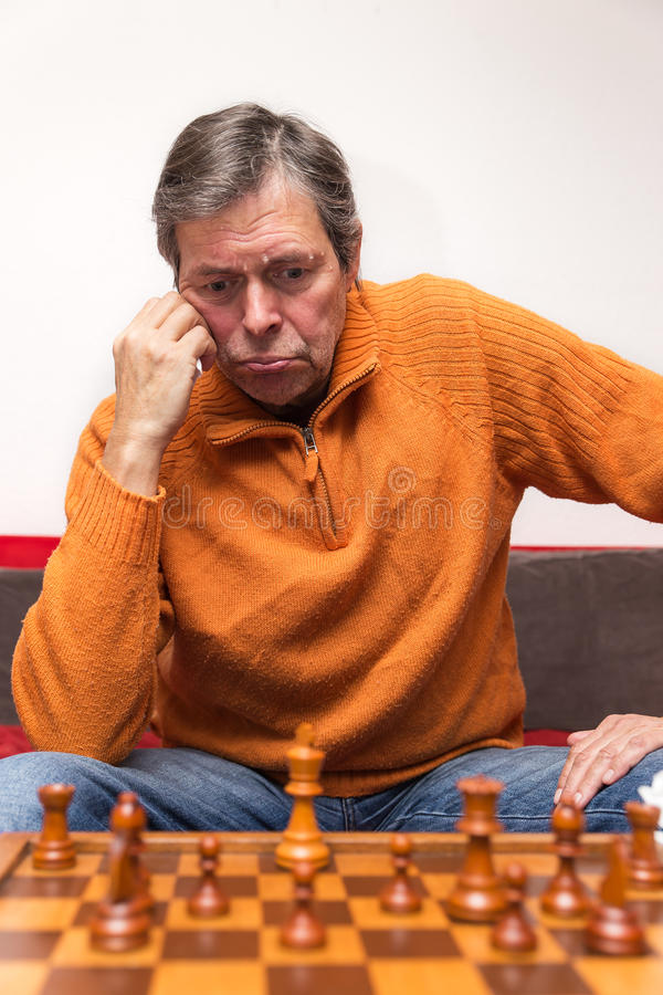 Senior citizen is playing chess. Portrait of an senior citizen, playing chess royalty free stock photo