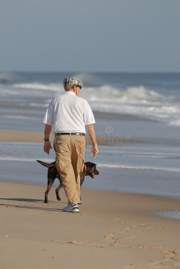Senior citizen walking beach royalty free stock image
