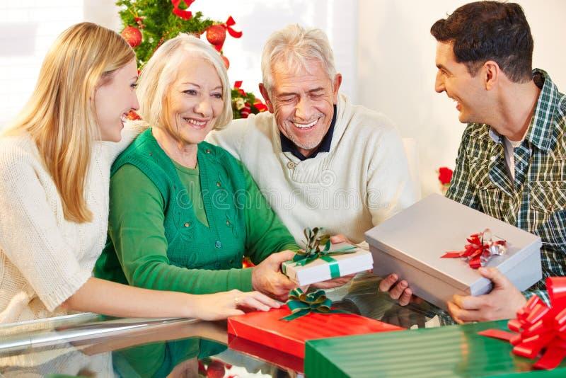 Senior citizens celebrating christmas with their children. Happy senior citizens celebrating christmas with their children and gifts royalty free stock images