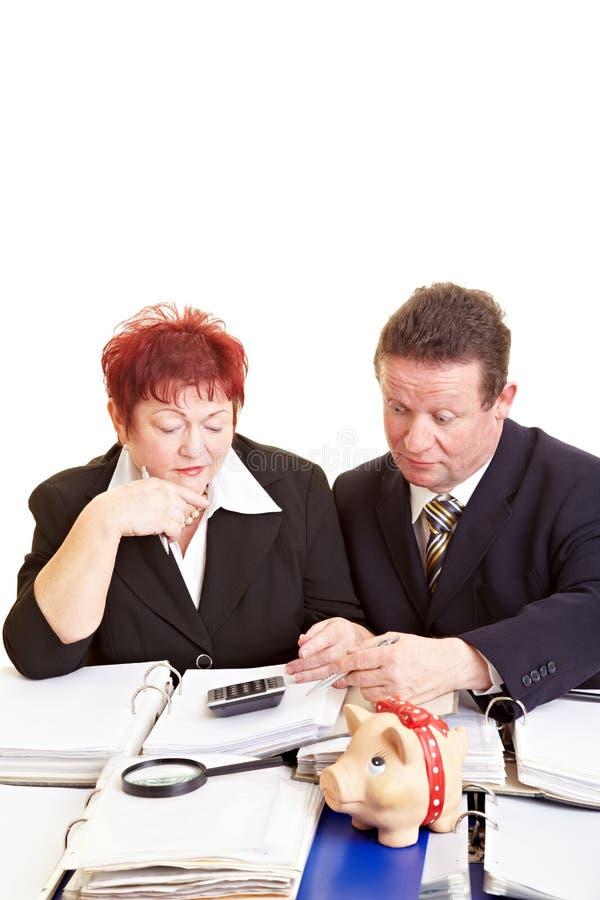 Senior citizens checking tax return. Senior citizens with files checking their tax return stock photos