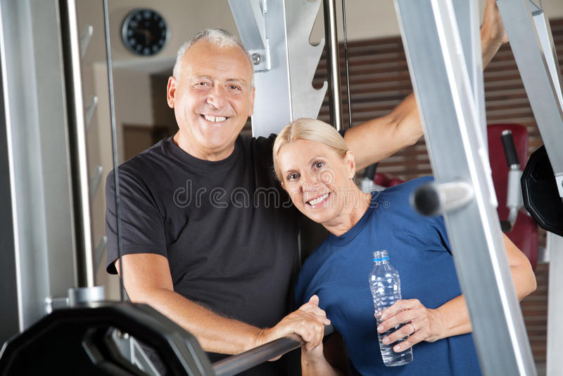 Senior citizens couple smiling. Happy senior citizens couple smiling in fitness center royalty free stock photos