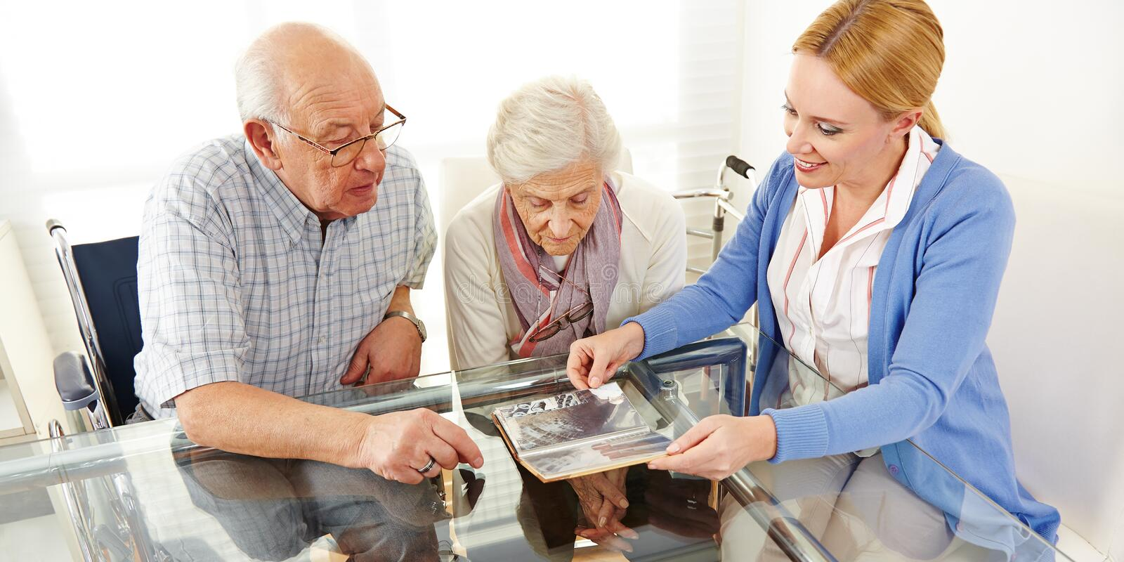 Senior citizens couple watching. A photo album with their daughter stock photo