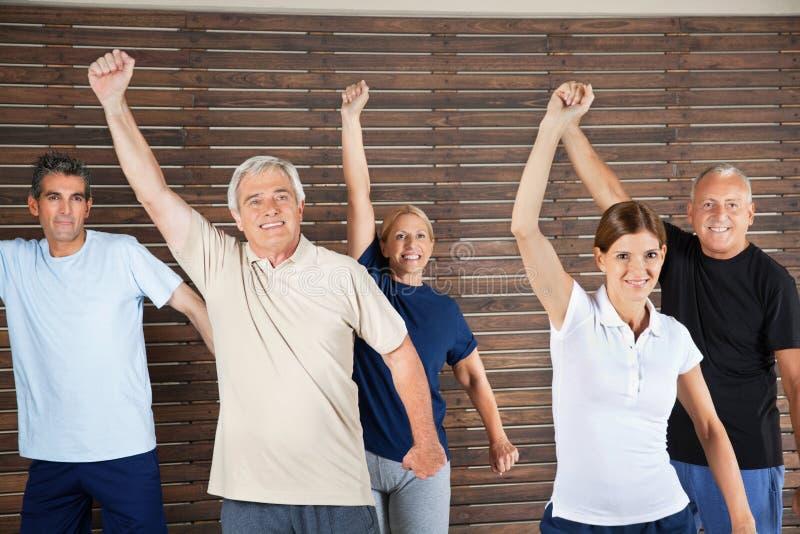 Senior citizens dancing to music. Happy senior citizens dancing to fitness music in gym stock image