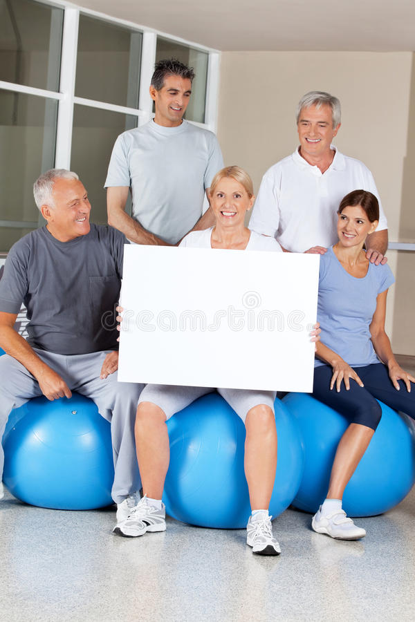 Senior citizens doing advertising for gym. Senior citizens on gym balls doing advertising for fitness center stock images