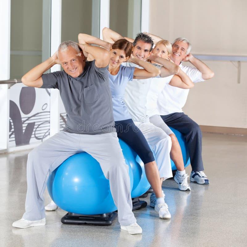 Senior citizens doing back. Happy senior citizens doing back exercises on gym ball in fitness center royalty free stock photography