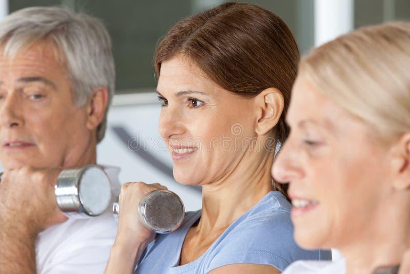 Senior citizens doing dumbbell. Training in fitness center royalty free stock photo