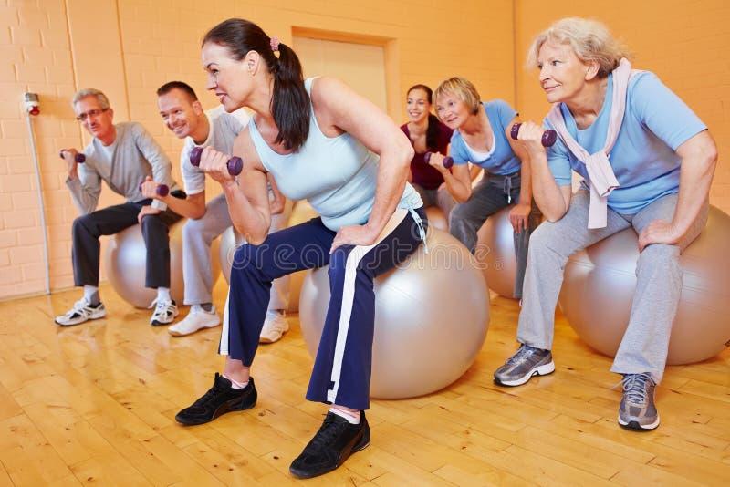 Senior citizens doing dumbbell. Group of senior citizens doing dumbbell training in gym stock photos