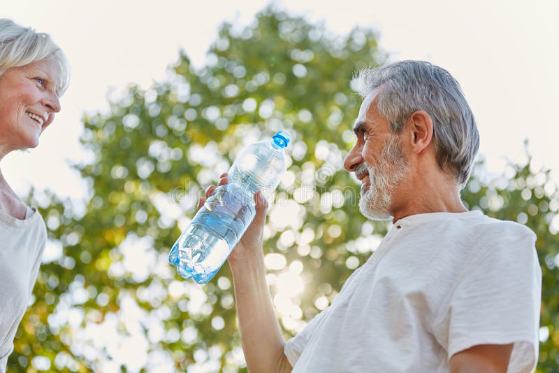 Senior citizens drinking from a water bottle. For refreshment in summer royalty free stock image