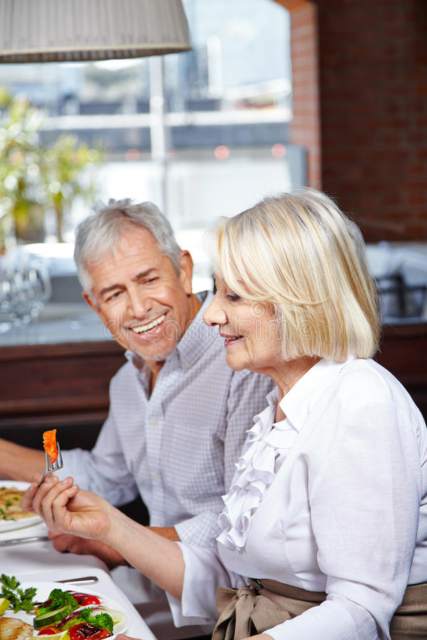 Senior citizens eating in nursing. Two happy senior citizens eating together in a nursing home royalty free stock image