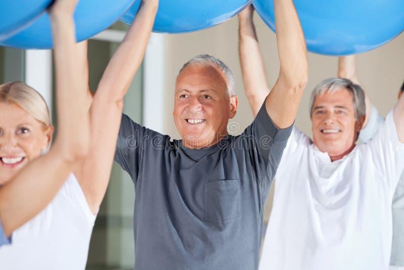 Senior citizens exercising with gym. Senior citizens exercising with blue gym balls in fitness center royalty free stock photography