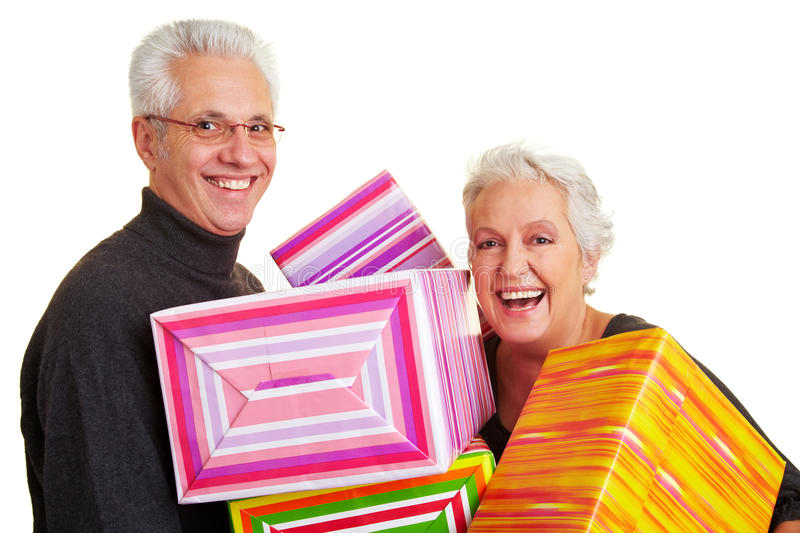 Senior citizens with gifts. Two happy senior citizens holding colorful gifts royalty free stock image