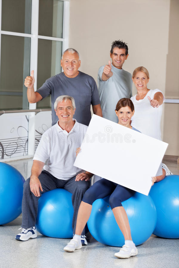 Senior citizens holding empty sign. Senior citizens on gym balls holding empty advertising sign in fitness center stock photo