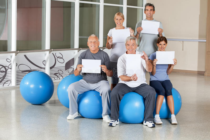 Senior citizens holding empty signs. Happy senior citizens on gym balls holding empty signs in fitness center royalty free stock photography