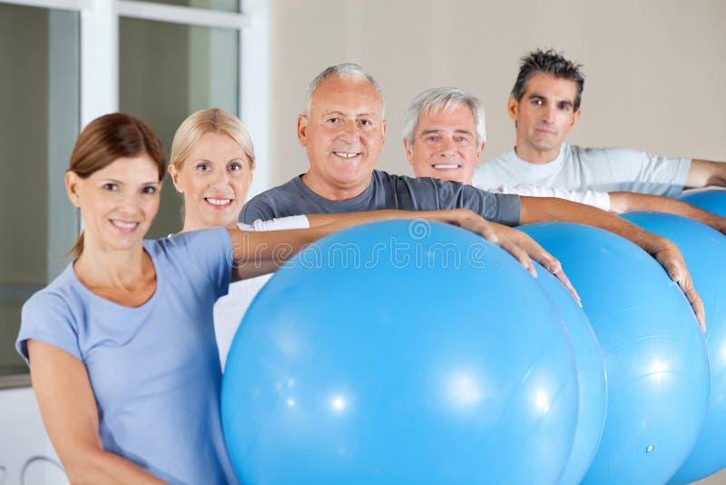 Senior citizens holding gym balls. Happy senior citizens holding blue gym balls in fitness center stock images