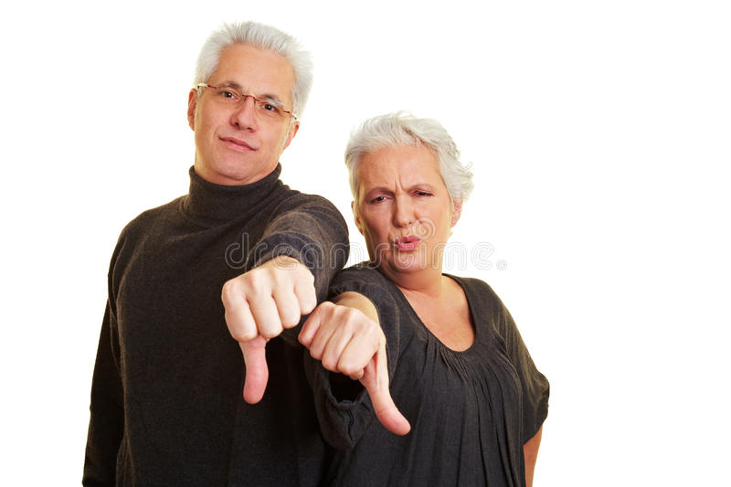 Senior citizens holding thumbs down. Two dissappointed senior citizens holding their thumbs down stock image