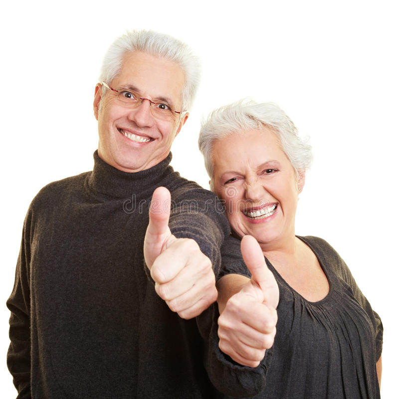 Senior citizens holding thumbs up. Two happy senior citizens holding their thumbs up royalty free stock images
