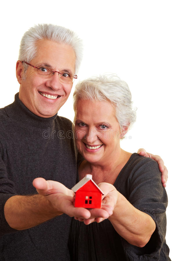 Senior citizens with house. Two happy senior citizens with small red house royalty free stock photos