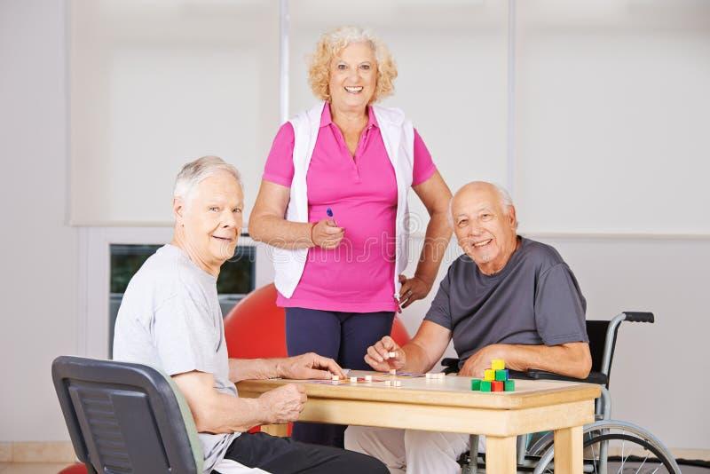 Senior citizens playing Bingo in nursing home. Three happy senior citizens playing Bingo together in a nursing home royalty free stock photos