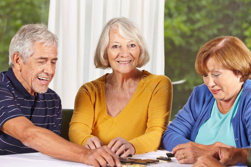 Senior citizens playing domino game. Three senior citizens playing a domino game in a nursing home stock photography