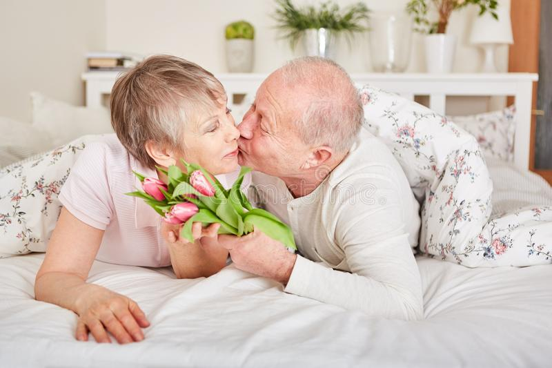 Senior citizens share kiss. On valentine`s day stock photos