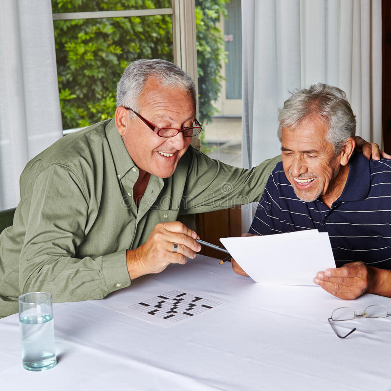 Senior citizens solving riddles. Two happy senior citizens solving riddles in a rest home royalty free stock photography