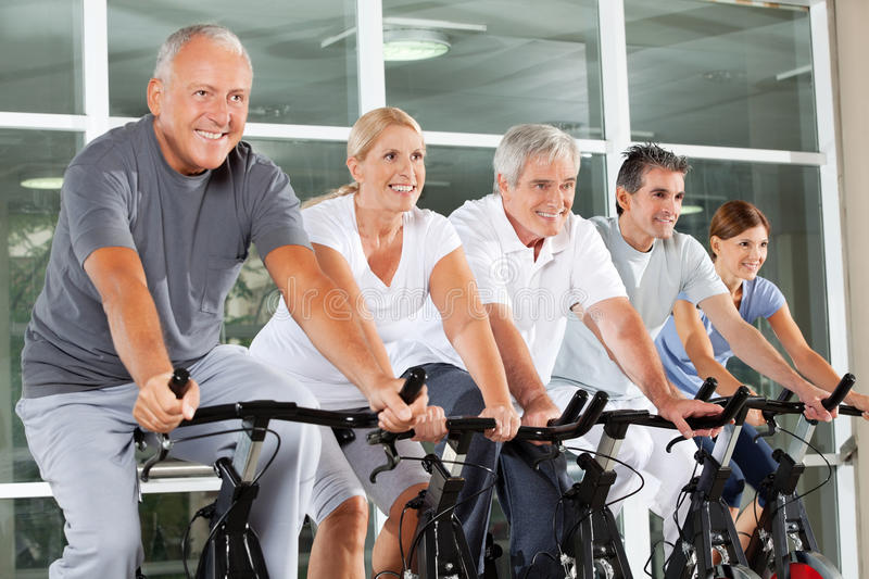 Senior citizens in spinning class. Happy senior citizens exercising in spinning class in fitness center royalty free stock photography