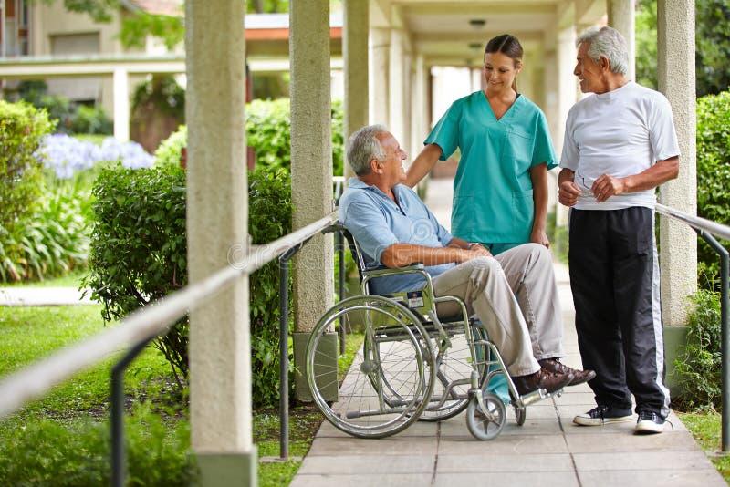 Senior citizens talking to nurse. Two senior citizens talking to a nurse in a hospital garden royalty free stock image