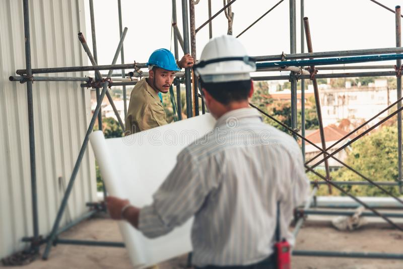 Senior civil engineer is reading drawing blueprint and supervision installing scaffolding work at construction site stock photo