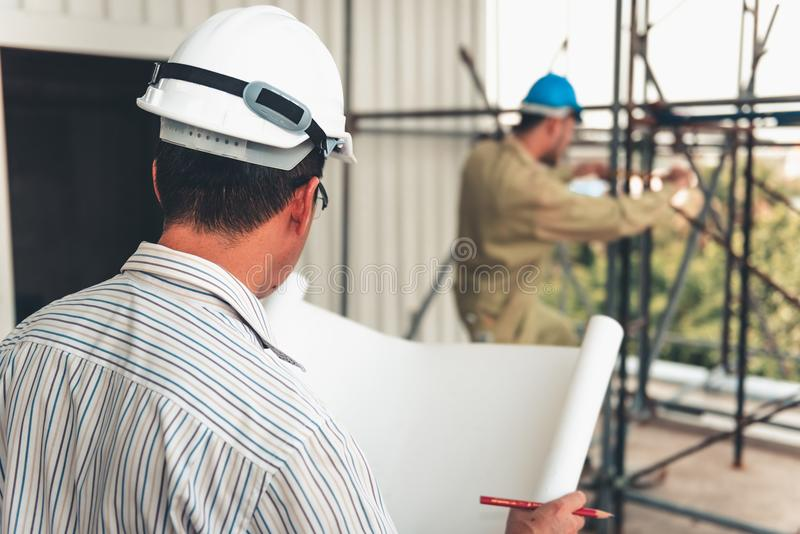 Senior civil engineer is reading drawing blueprint and supervision work at construction site royalty free stock photos
