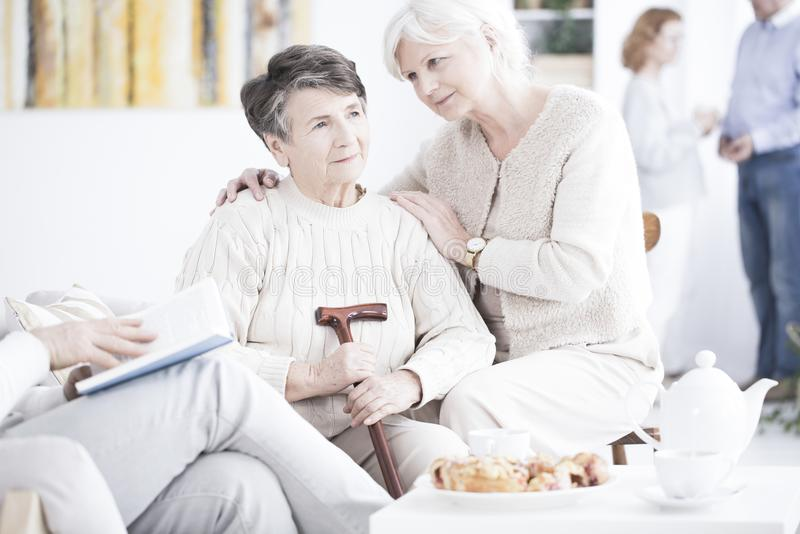 Senior comforting her friend. A senior sitting and comforting her friend looking ahead and holding a walking cane stock image