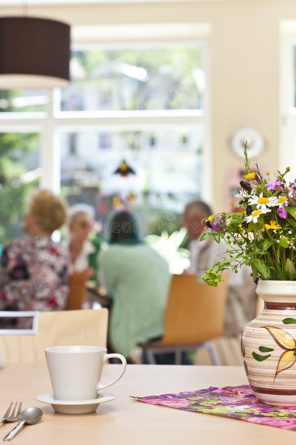 Senior Community in a retirement home. Defocused senior community in a retirement home having breakfast stock photo
