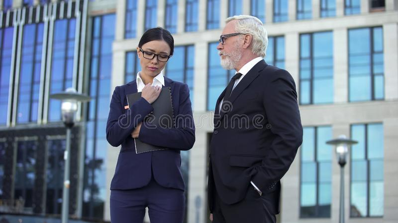 Senior company director looking angrily at female assistant, project failure royalty free stock image