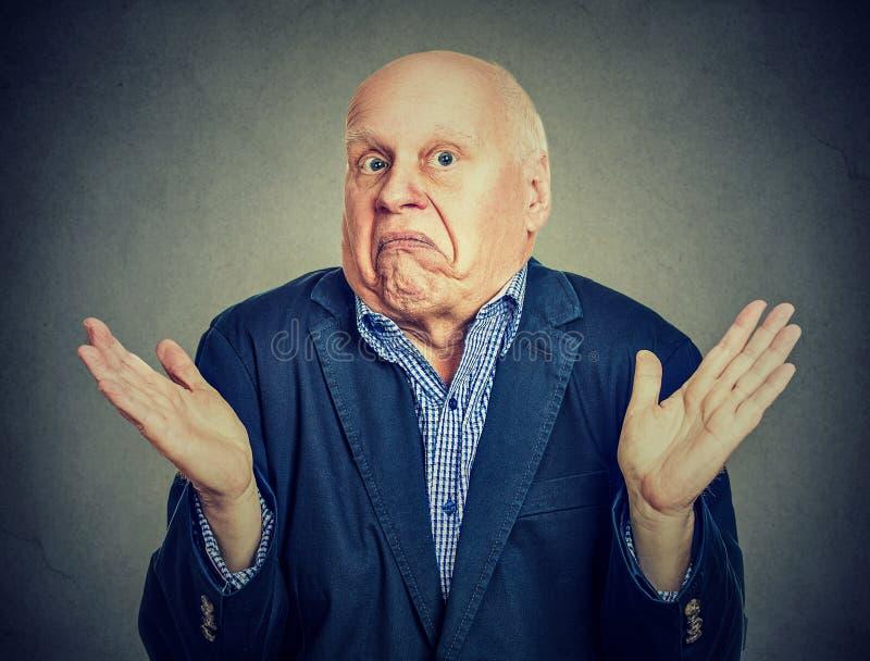Senior confused man is shrugging his shoulders. Senior confused man shrugging shoulders stock photography