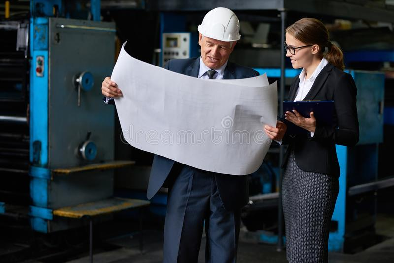 Senior Construction Inspector Proofing Factory Plans. Portrait of senior businessman looking at floor plans of modern factory with young assistant manager royalty free stock photography