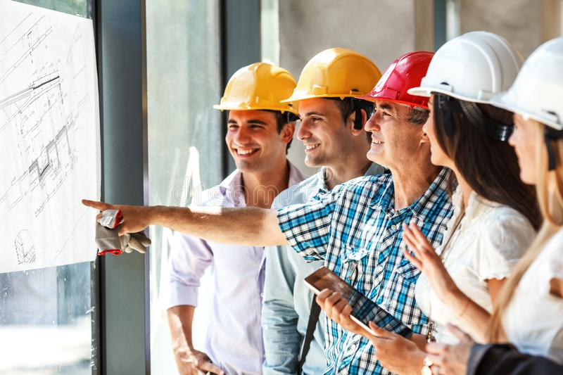 Senior construction manager and group of architects and experts discuss about construction project. Group of architects and experts discuss about construction royalty free stock photo