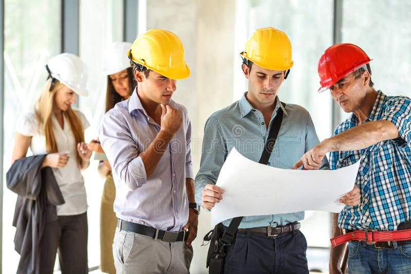 Senior construction manager and group of architects and experts discuss about construction project. Group of architects and experts discuss about construction stock photography