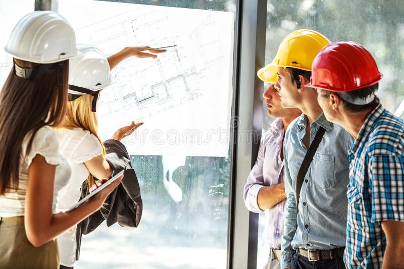 Senior construction manager and group of architects and experts discuss about construction project. Group of architects and experts discuss about construction royalty free stock photos