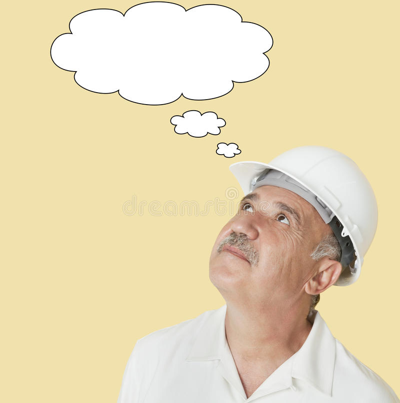 Senior construction worker with hardhat looking up over yellow background stock images