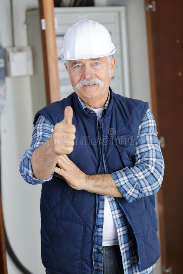 Senior construction worker looking at plans on job stock image